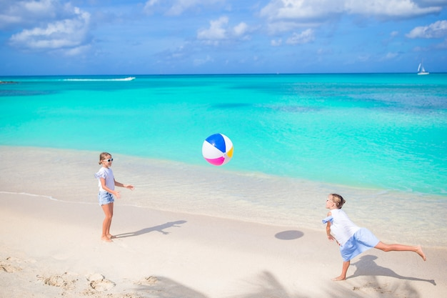 Little adorable girls playing with ball on the beach. kids having fun on the seashore