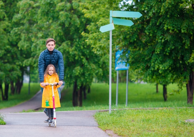Little adorable girls riding on scooters with dad in autumn park outdoors