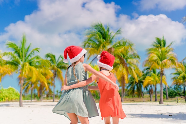 Little adorable girls in santa hats during beach vacation have fun together