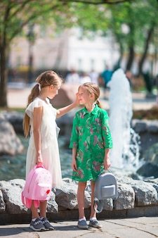 Little adorable girls in warm day outdoor in the city