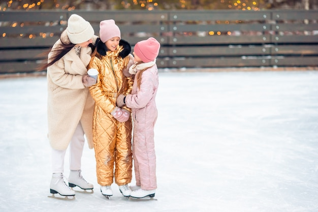 Little adorable girls with her mother skating on ice-rink