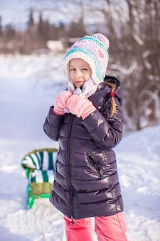 Little adorable happy girl in the snow sunny winter day