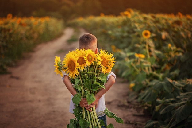 Little adorable kid boy holding bouquet of sunflowers in summer day.