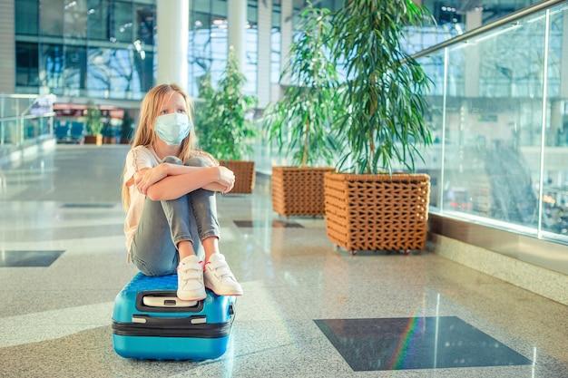 国際空港でサージカルマスクの顔の保護を持つ愛らしい子供。コロナウイルスとグリップに対する保護