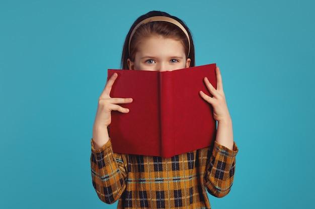 Маленькая очаровательная школьница прячется за книгой с радостным выражением лица