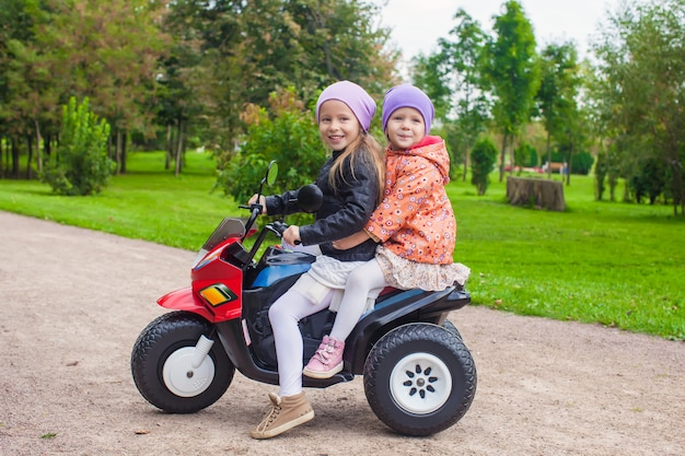 Little adorable sisters sitting on toy motorcycle in green park