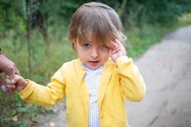 여름 들판에서 시골길을 걷고 있는 작고 사랑스러운 유아. 시골에서 어린이 휴가