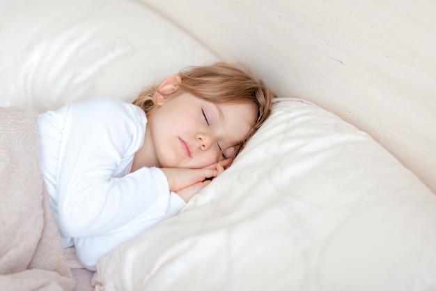 白い服を着た小さな愛らしいブロンドの女の子は、快適な枕の上でベッドで寝ています