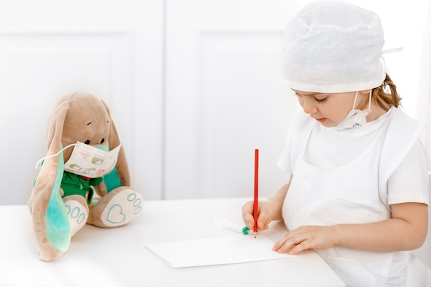 医師を演じる医療マスクの小さな愛らしい子供の女の子が患者に処方箋を記入します