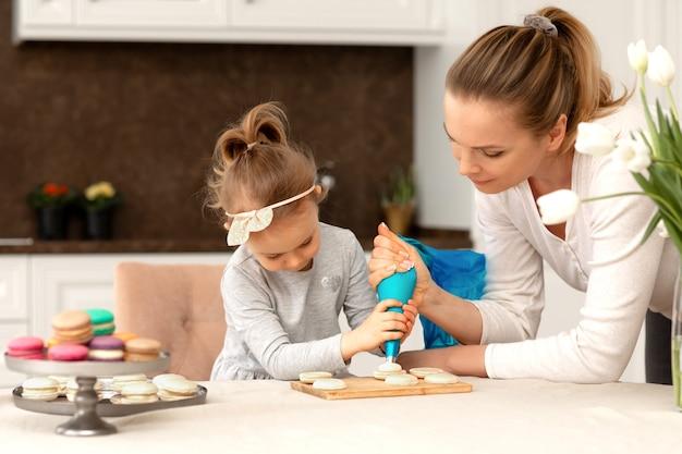 작은 사랑스러운 소녀와 그녀의 어머니는 마카롱을 굽고 부엌에서 쿠키를 요리합니다.