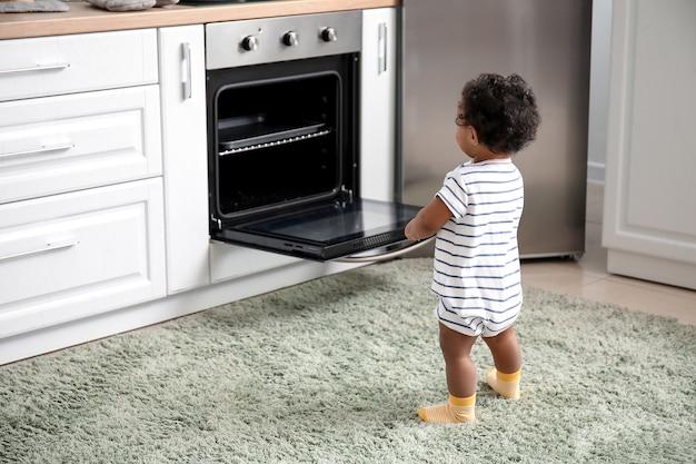 キッチンのストーブの近くの小さなアフリカ系アメリカ人の赤ちゃん。危険にさらされている子供