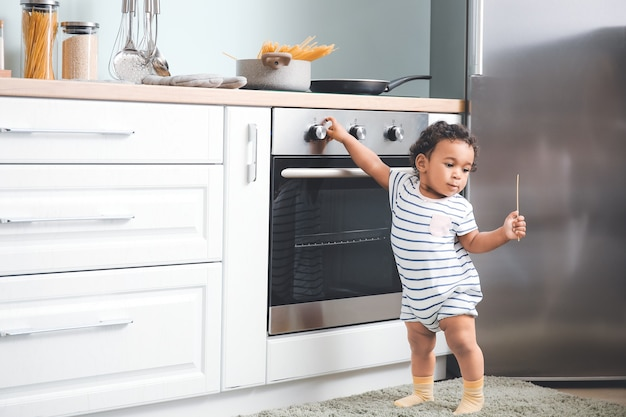 Little african-american baby near stove in kitchen. child in danger