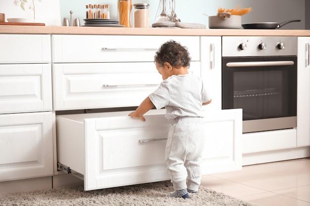 キッチンで遊んでいる小さなアフリカ系アメリカ人の赤ちゃん。危険にさらされている子供