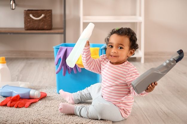 Little african-american baby playing with cleaning supplies at home. child in danger