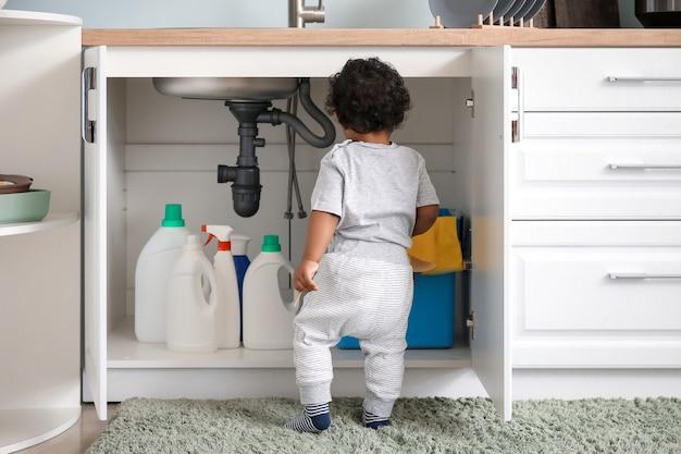 Маленький афро-американский ребенок играет с моющими средствами дома. ребенок в опасности