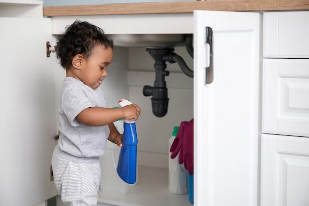 家で洗剤で遊んでいる小さなアフリカ系アメリカ人の赤ちゃん。危険にさらされている子供