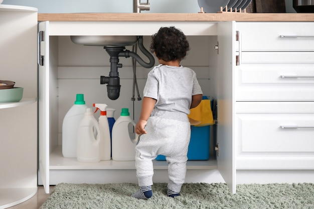 Little african-american baby playing with detergents at home. child in danger