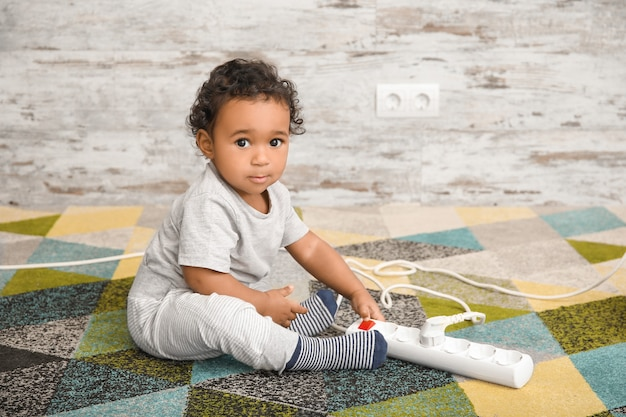 연장 코드 집에서 놀고 작은 아프리카 계 미국인 아기. 위험에 처한 어린이