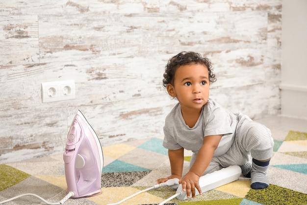 철 집에서 놀고 작은 아프리카 계 미국인 아기. 위험에 처한 어린이