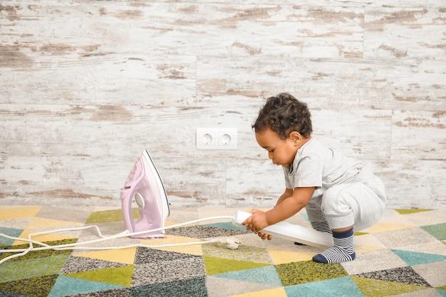 Маленький афро-американский ребенок играет с железом дома. ребенок в опасности