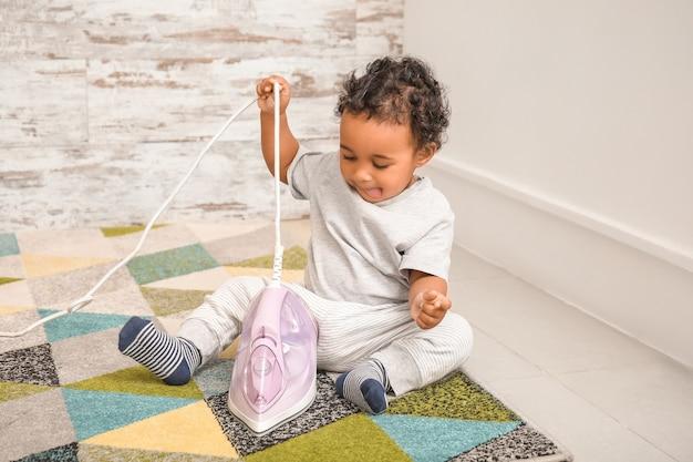 家で鉄で遊んでいる小さなアフリカ系アメリカ人の赤ちゃん。危険にさらされている子供