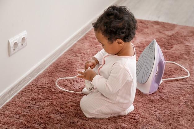 Маленький афро-американский ребенок играет с розеткой и утюгом дома. ребенок в опасности