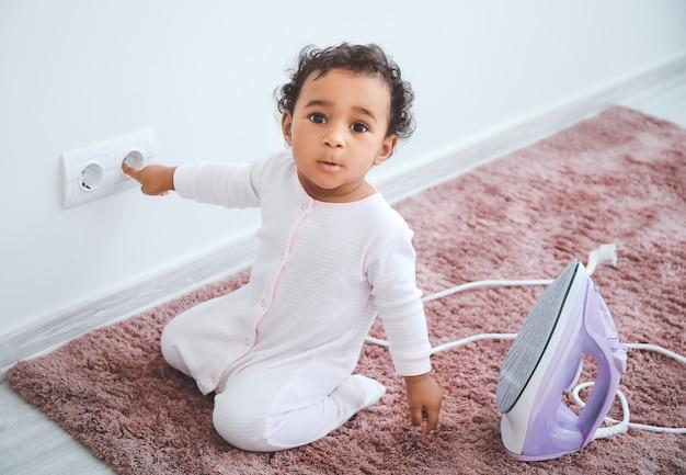 家でソケットとアイロンで遊んでいる小さなアフリカ系アメリカ人の赤ちゃん。危険にさらされている子供