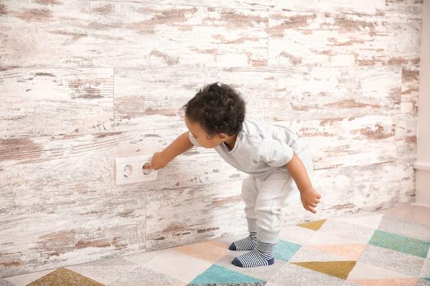 Маленький афро-американский ребенок играет с розеткой дома. ребенок в опасности