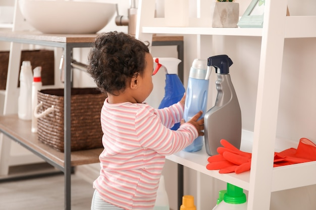Little african-american baby playing with washing liquids at home. child in danger