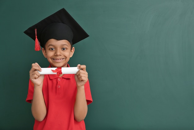 Little african-american boy in graduation hat and with diploma near chalkboard