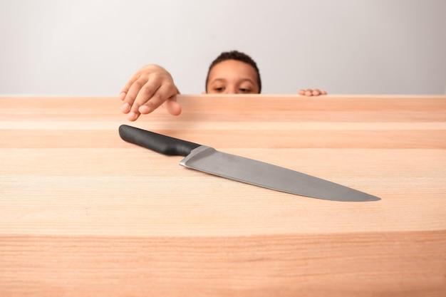 ナイフでテーブルの近くに小さなアフリカ系アメリカ人の少年。危険にさらされている子供