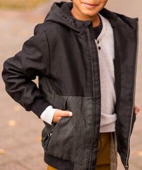 Маленький афро-американский мальчик позирует на городской улице в осенней одежде. фото