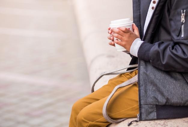 Маленький афро-американский мальчик позирует на городской улице в осенней одежде с чашкой горячего шоколада в руках. фото