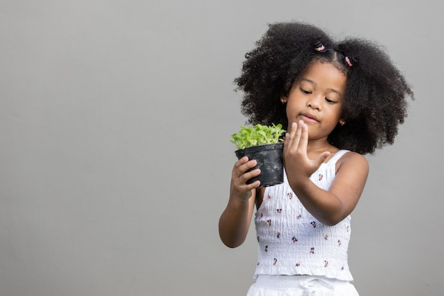 Little african american curly hair girl holding sprout salad and compare height by hand