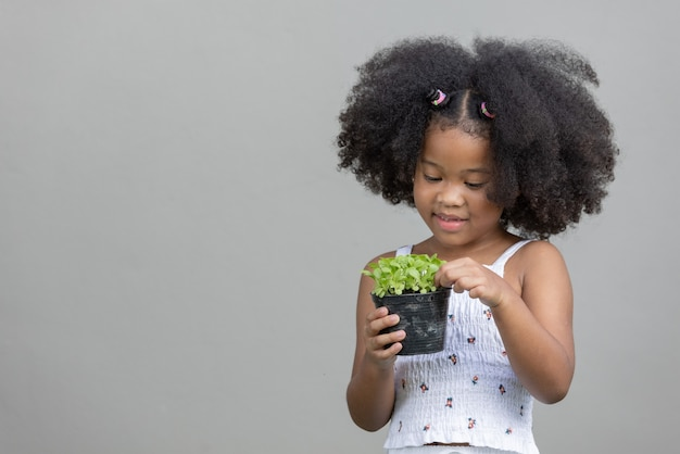 Little african american curly hair girl holding sprout salad