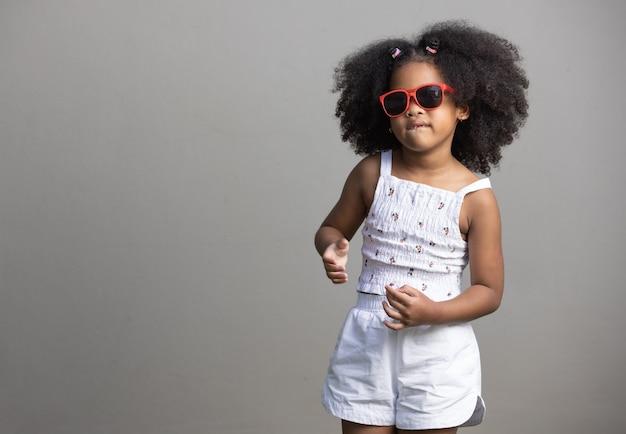 Маленькая афроамериканская девушка с вьющимися волосами в красных солнцезащитных очках и танцующая хип-хоп