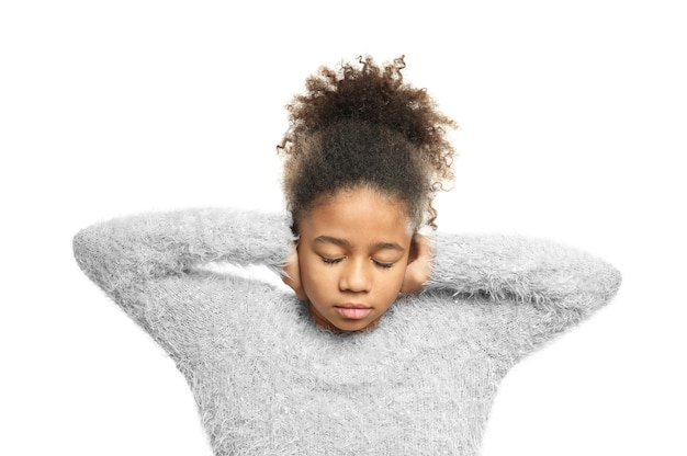 白い背景で彼女の耳を覆っている小さなアフリカ系アメリカ人の女の子。聴覚障害