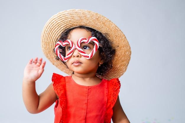 빨간 여름 옷에 작은 아프리카 계 미국인 여자와 스튜디오에서 흰색 배경에 밀짚 모자