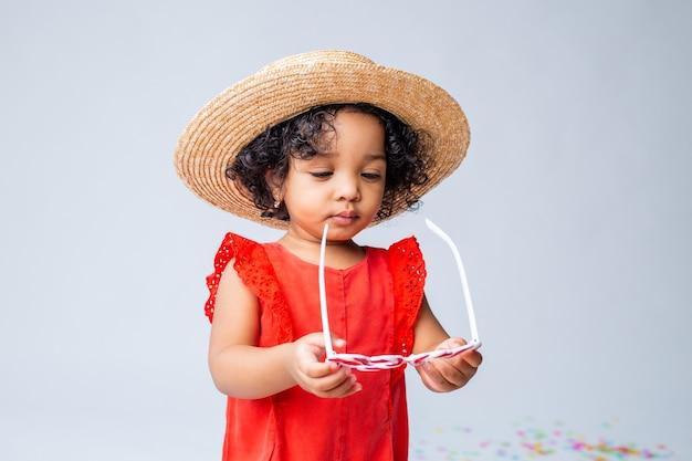 Маленькая афроамериканская девочка в красной летней одежде и соломенной шляпе на белом фоне в студии