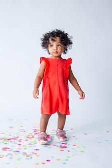 스튜디오에서 흰색 배경에 빨간색 여름 옷에 작은 아프리카 계 미국인 여자