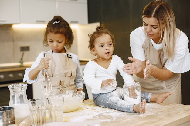Little african-american girl mixing dough in a glass bowl, preparing a cake. her sister toddler sitting on a table. their mother teaching them.