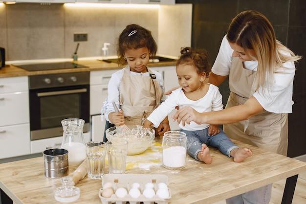 Маленькая афро-американская девочка, замешивая тесто в стеклянной миске, готовит торт. ее младшая сестра сидит на столе. их мать учит их.