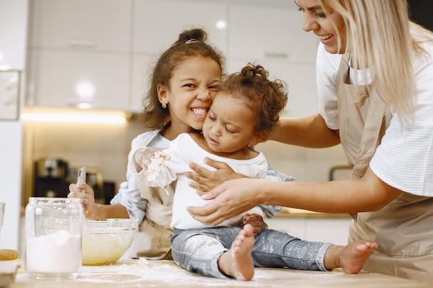 ガラスのボウルに生地を混ぜてケーキを準備するアフリカ系アメリカ人の少女。テーブルの上に座っている彼女の妹の幼児。彼らの母親は彼らに教えています。