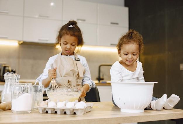 Маленькая афро-американская девочка, замешивая тесто в стеклянной миске, готовит торт. ее младшая сестра сидит на столе.