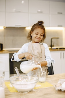 Little african-american girl pouring milk in a glass bowl, preparing a dough.