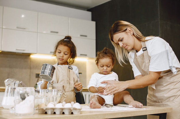 Little african-american girl preparing a cake. her sister toddler sitting on a table. their mother teaching them.