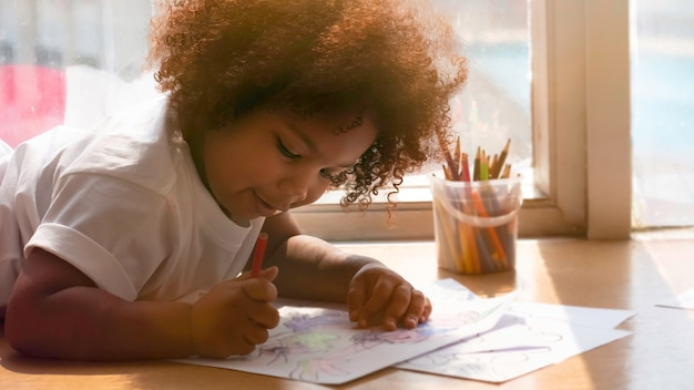 Little african girl painting and drawing with happiness.