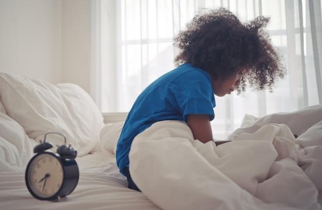 작은 아프리카의 아이가 알람 시계로 깨어났습니다.