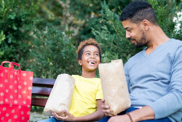 Little afro american girl eating popcorn with her father in park