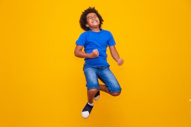 Маленький афро мальчик прыгает на желтом фоне.